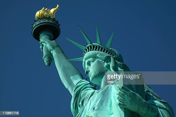 A closeup, upward pointing view of the Statue of Liberty