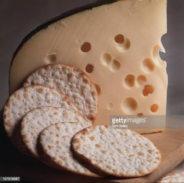 Closeup view of a wedge of swiss cheese and crackers arranged on a wooden tray 2004