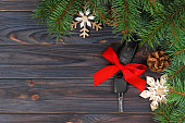 Close-up view of car keys with red bow as present on wooden background.