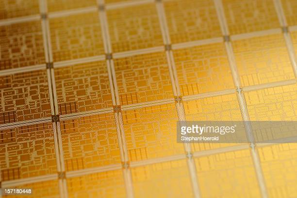 Close-up view of chip wafer with regular pattern in gold