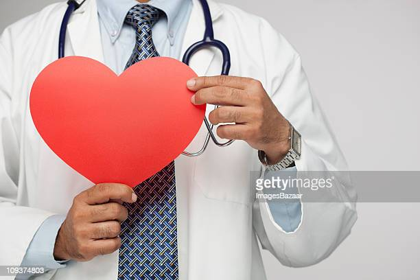 Close-up view of doctor holding red heart