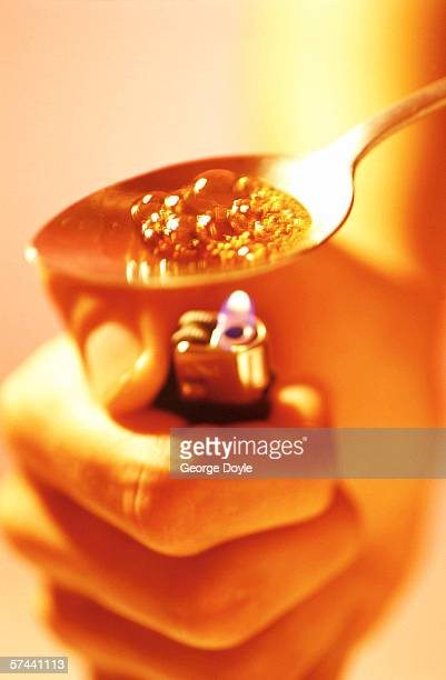 close-up view of hand lighting up drug in spoon