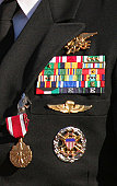 Close-up view of military decorations and honors on a commander's dress uniform.