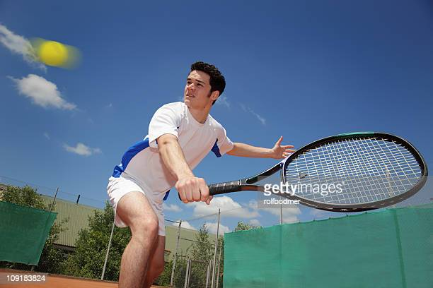 Close-up view of tennis player reaching a ball