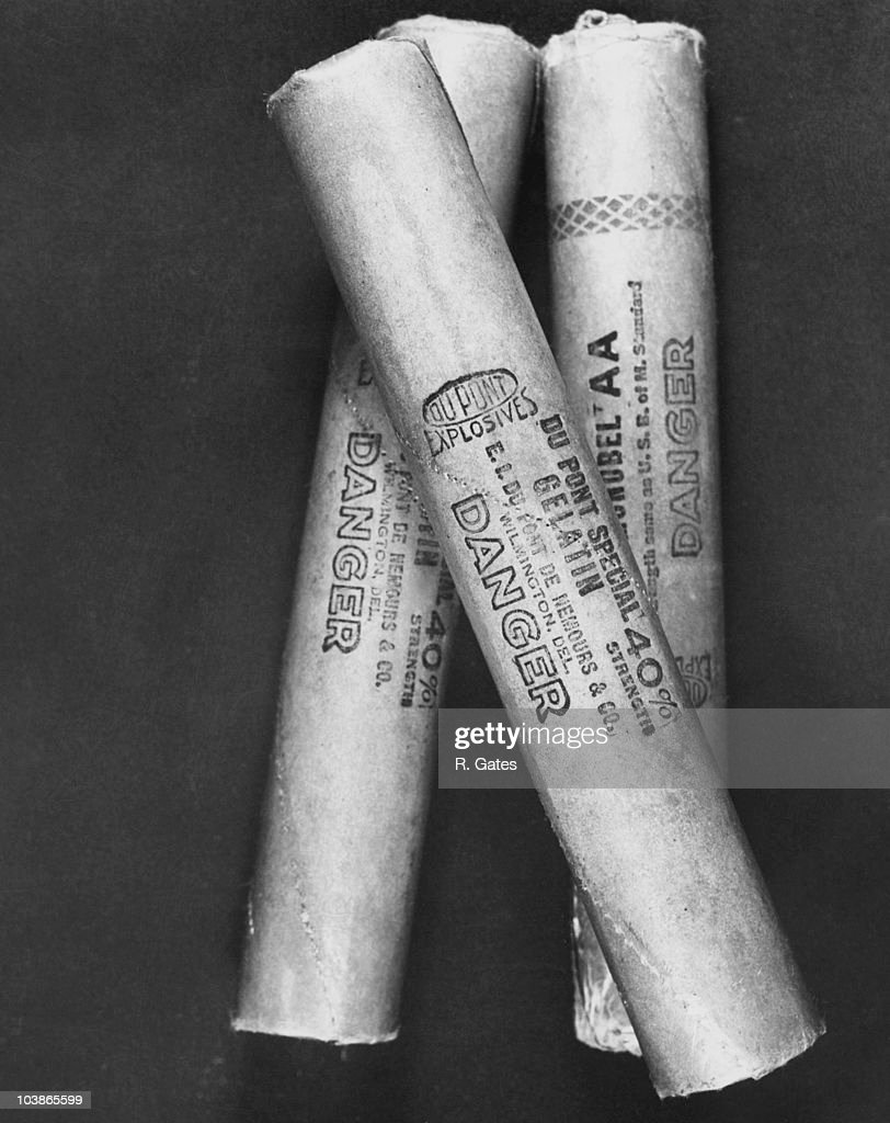 Closeup view of three sticks of dynamite produced by DuPont Explosives USA circa 1950 Each stick has 'Du Pont Explosives Du Pont Special Gelatin 40%...