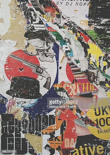 Close-Up View Of Torn Posters On Wall