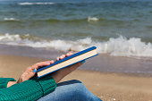 Closeup view of two white female hands holding thick blue book. Woman reading at sea beach on sunny spring, autumn or cool summer day during beach holidays.