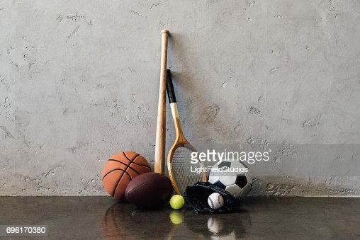 Close-up view of various balls and sports equipment near grey wall : Stock Photo