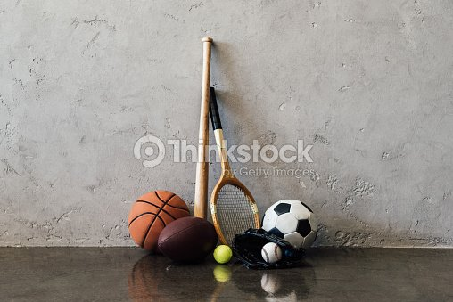 Vue rapprochée de plusieurs balles et équipement près de mur gris de sport : Photo