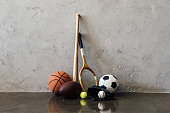Close-up view of various balls and sports equipment near grey wall