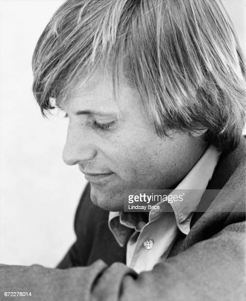 Closeup view of Viggo Mortensen dressed in a buttondown shirt and sport coat seated with his left elbow up toward camera his eyes look downward to...