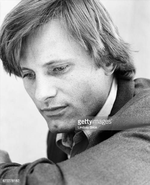 Closeup view of Viggo Mortensen dressed in a buttondown shirt and sport coat seated with one elbow on his knee he looks downward to his left during a...