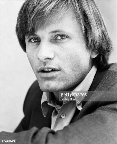 Closeup view of Viggo Mortensen dressed in a buttondown shirt and sport coat seated his left elbow across his knee he looks upward to his left in a...