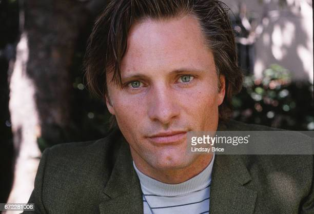 Closeup view of Viggo Mortensen wearing a green sport coat and light blue striped tee as he looks directly into the lens during a photo shoot on...