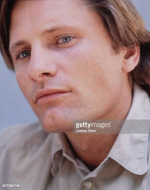 Closeup view of Viggo Mortensen wearing a tan buttondown shirt he tilts his chin slightly upward as he looks past the lens to his left during a photo...