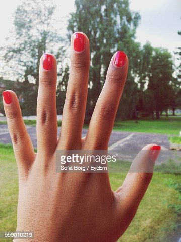 Close-Up View Of Woman With Red Nails