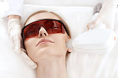 Close-up view of young woman in uv protective glasses receiving laser skin care on face