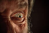 Close-up view on the screwed-up eye of senior or mature man. Elderly caucasian model. Gray angry eye with red veins. Old wrinkles close-up. Human emotions and facial expressions concept