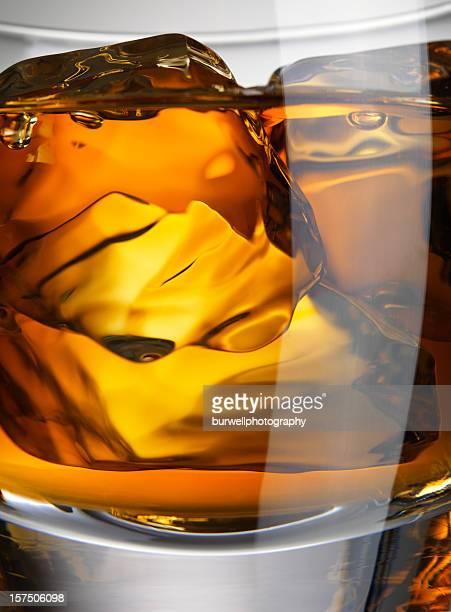 Primo piano di vetro di whisky con cubetti di ghiaccio