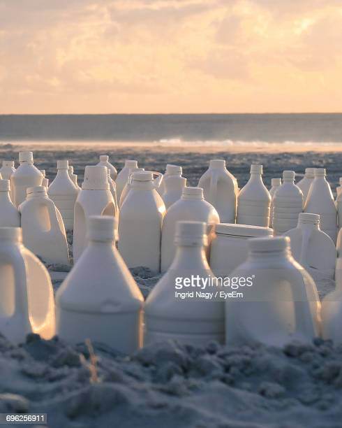 Close-Up White Gallons On Beach Against Sky During Sunset
