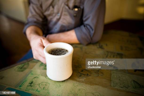 A close-up with a man holding a cup of coffee