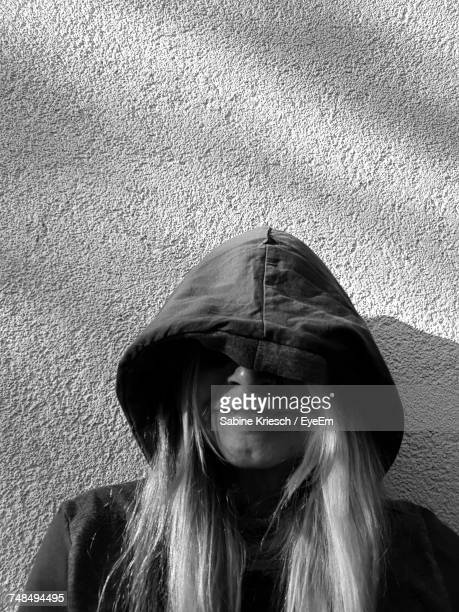 Close-Up Woman Wearing Hood Against Wall