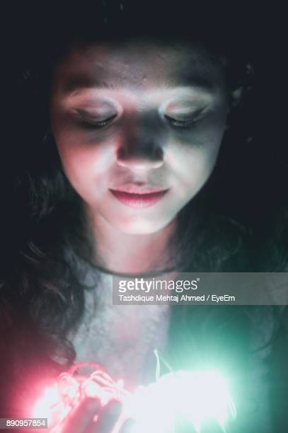 Close-Up Young Woman With Illuminated Lights In Darkroom