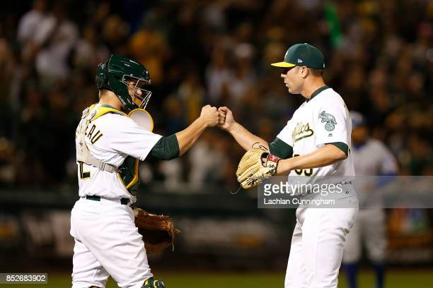 Closing pitcher Blake Treinen of the Oakland Athletics celebrates with Dustin Garneau after a win against the Texas Rangers at Oakland Alameda...
