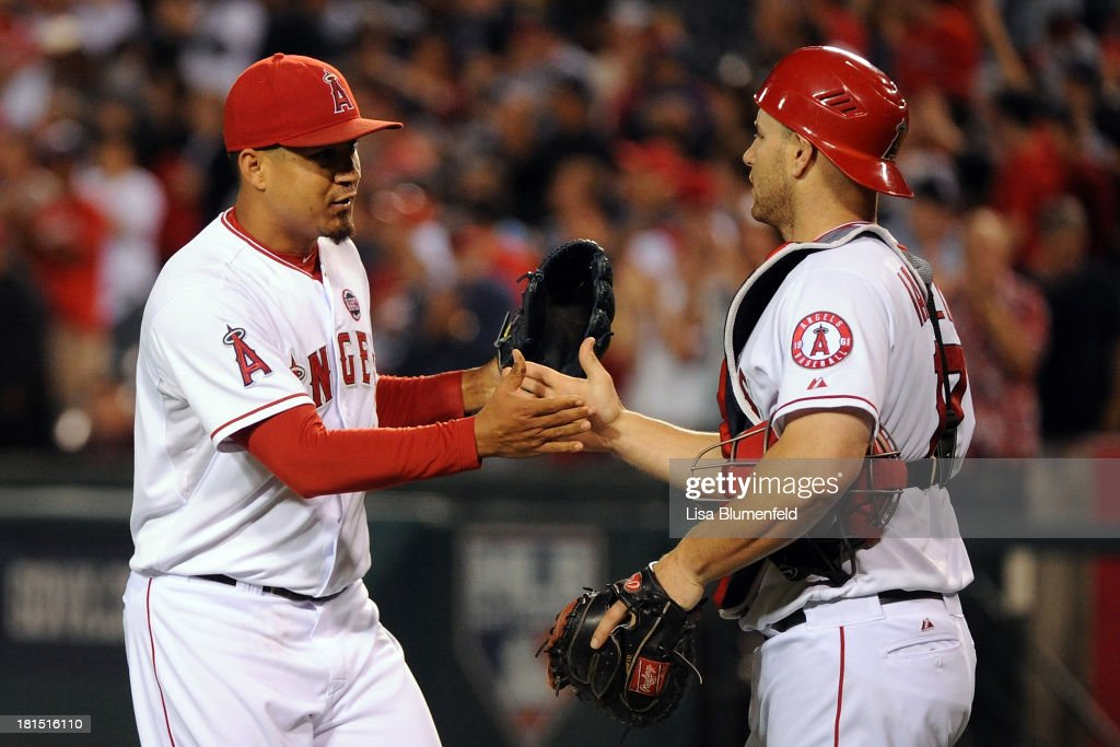 Closing pitcher Ernesto Frieri #49 and teammate catcher Chris Iannetta #17 of the Los Angeles Angels of Anaheim celebrate defeating the Seattle Mariners 5-6 at Angel Stadium of Anaheim on September 21, 2013 in Anaheim, California.