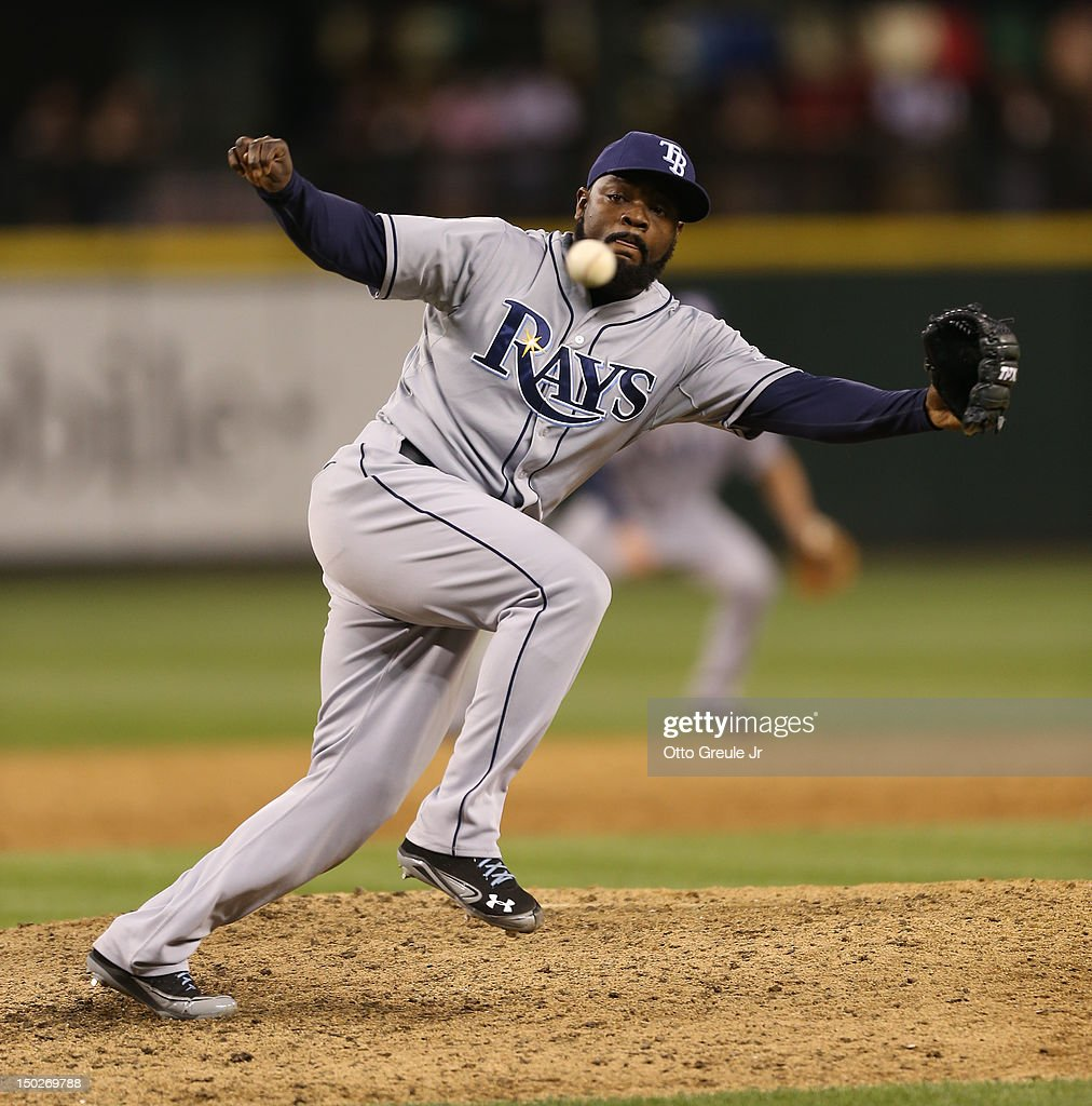 Closing pitcher <a gi-track='captionPersonalityLinkClicked' href=/galleries/search?phrase=Fernando+Rodney&family=editorial&specificpeople=547291 ng-click='$event.stopPropagation()'>Fernando Rodney</a> #56 of the Tampa Bay Rays reaches for a single by Kyle Seager of the Seattle Mariners at Safeco Field on August 13, 2012 in Seattle, Washington. The Rays defeated the Mariners 4-1.