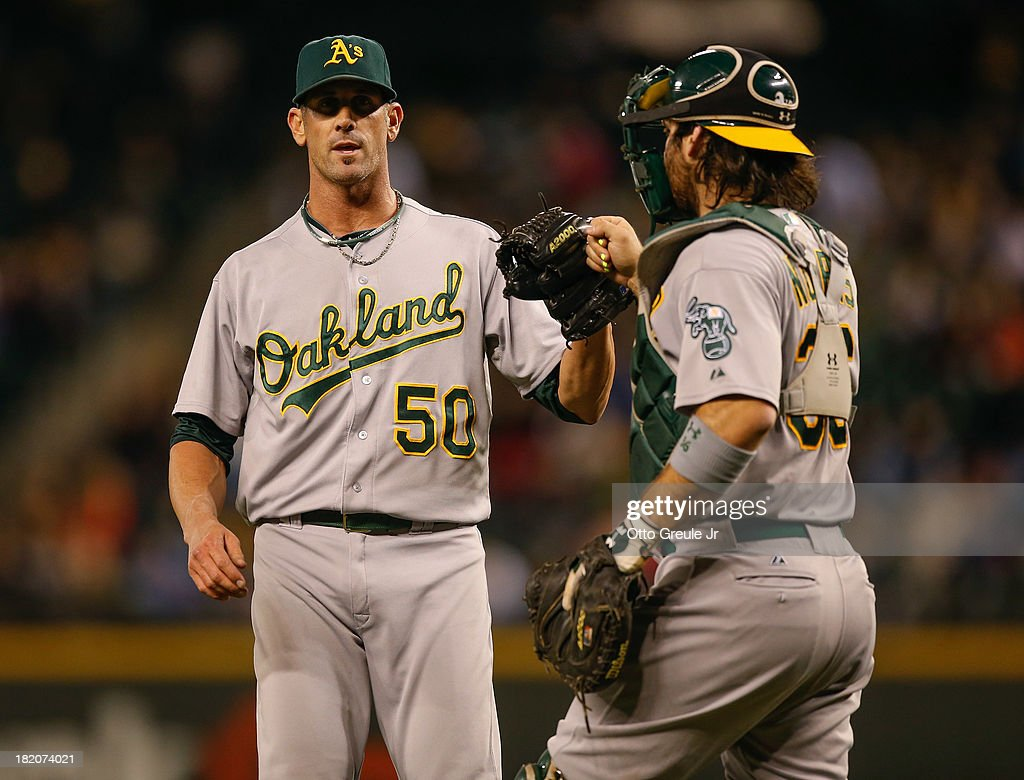 Closing pitcher <a gi-track='captionPersonalityLinkClicked' href=/galleries/search?phrase=Grant+Balfour&family=editorial&specificpeople=833980 ng-click='$event.stopPropagation()'>Grant Balfour</a> #50 of the Oakland Athletics celebrates with catcher <a gi-track='captionPersonalityLinkClicked' href=/galleries/search?phrase=Derek+Norris&family=editorial&specificpeople=6795804 ng-click='$event.stopPropagation()'>Derek Norris</a> #36 after defeating the Seattle Mariners 8-2 at Safeco Field on September 27, 2013 in Seattle, Washington.