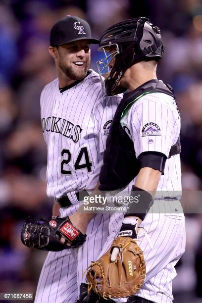 Closing pitcher Jordan Lyles and catcher Dustin Garneau of the Colorado Rockies celebrate their win over the San Francisco Giants at Coors Field on...