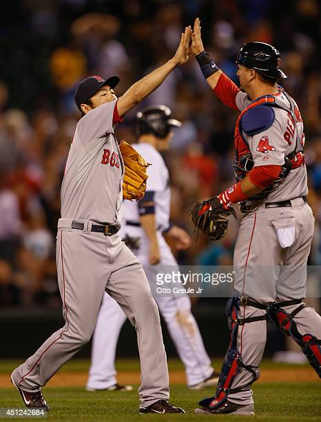 Closing pitcher Koji Uehara of the Boston Red Sox is congratulated by catcher AJ Pierzynski after defeating the Seattle Mariners 54 at Safeco Field...