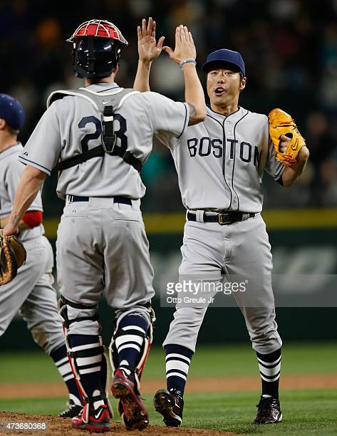 Closing pitcher Koji Uehara of the Boston Red Sox is congratulated by catcher Blake Swihart after defeating the Seattle Mariners 42 at Safeco Field...
