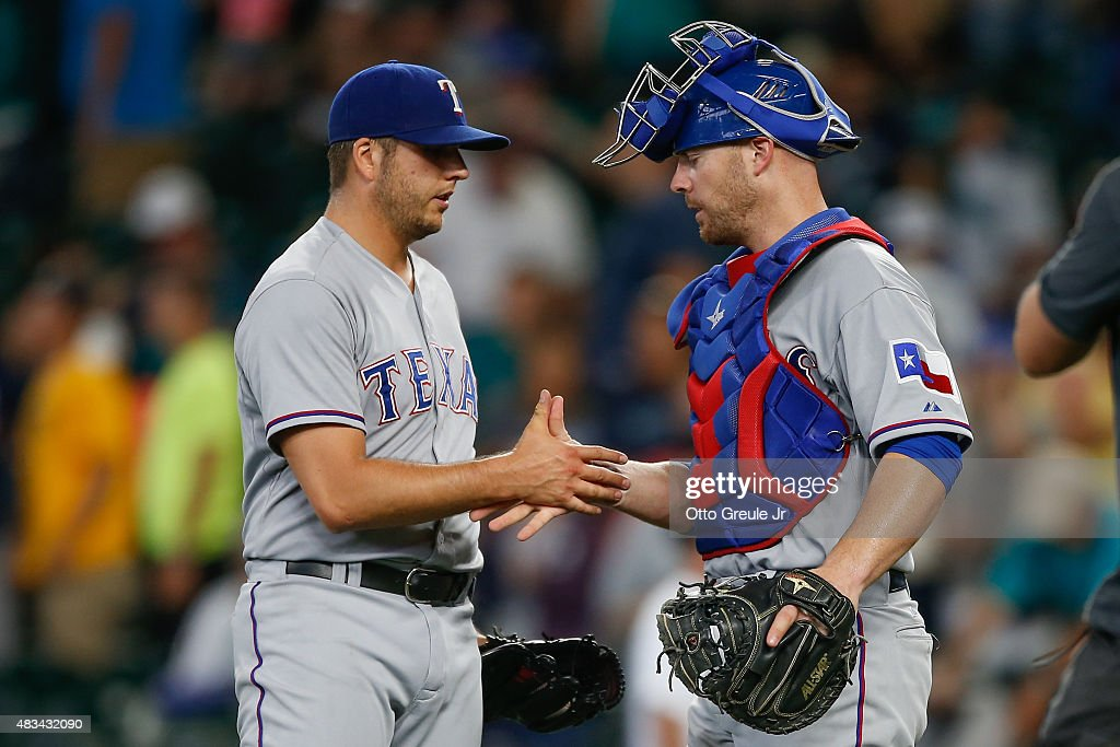 Closing pitcher Shawn Tolleson #37 of the Texas Rangers is congratulated by catcher Chris Gimenez #38 after defeating the Seattle Mariners 11-3 at Safeco Field on August 8, 2015 in Seattle, Washington.