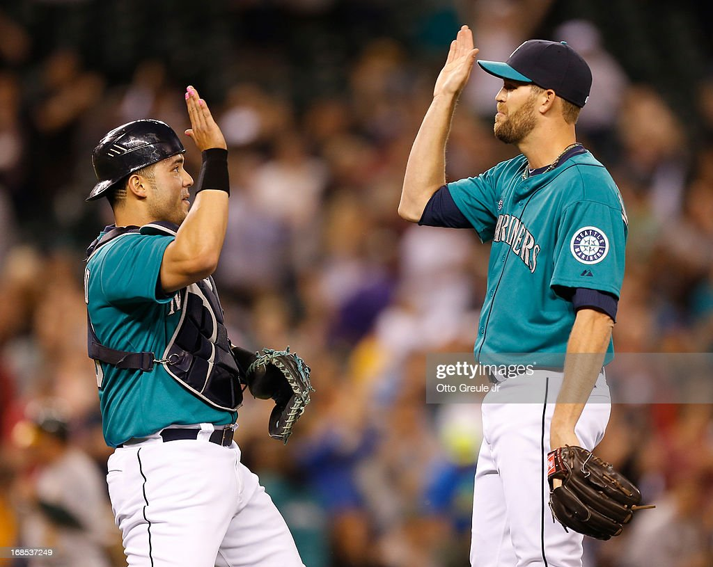 Closing pitcher Tom Wilhelmsen #54 (R) of the Seattle Mariners celebrates with catcher <a gi-track='captionPersonalityLinkClicked' href=/galleries/search?phrase=Jesus+Montero&family=editorial&specificpeople=4900196 ng-click='$event.stopPropagation()'>Jesus Montero</a> #63 after defeating the Oakland Athletics 6-3 at Safeco Field on May 10, 2013 in Seattle, Washington.
