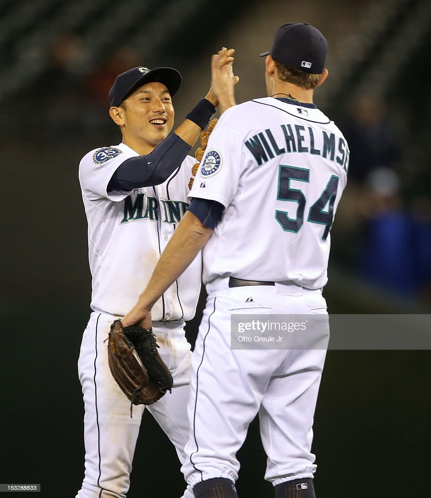 Closing pitcher Tom Wilhelmsen #54 of the Seattle Mariners is congratulated by Munenori Kawasaki #61 after defeating the Los Angeles Angels of Anaheim 6-1 at Safeco Field on October 2, 2012 in Seattle, Washington.