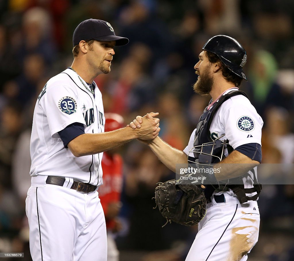 Closing pitcher Tom Wilhelmsen #54 of the Seattle Mariners is congratulated by catcher John Jaso #27 after defeating the Los Angeles Angels of Anaheim 6-1 at Safeco Field on October 2, 2012 in Seattle, Washington.