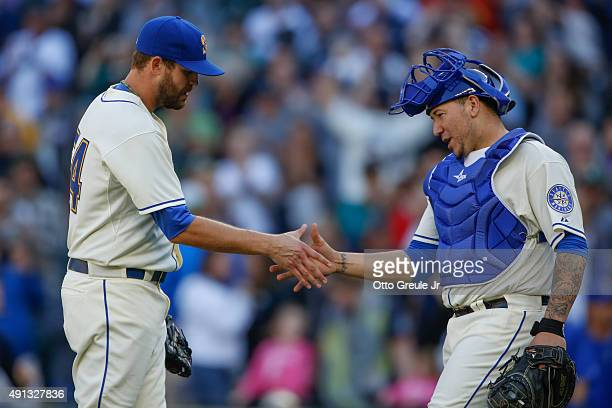 Closing pitcher Tom Wilhelmsen of the Seattle Mariners is congratulated by catcher Jesus Sucre after defeating the Oakland Athletics 32 at Safeco...