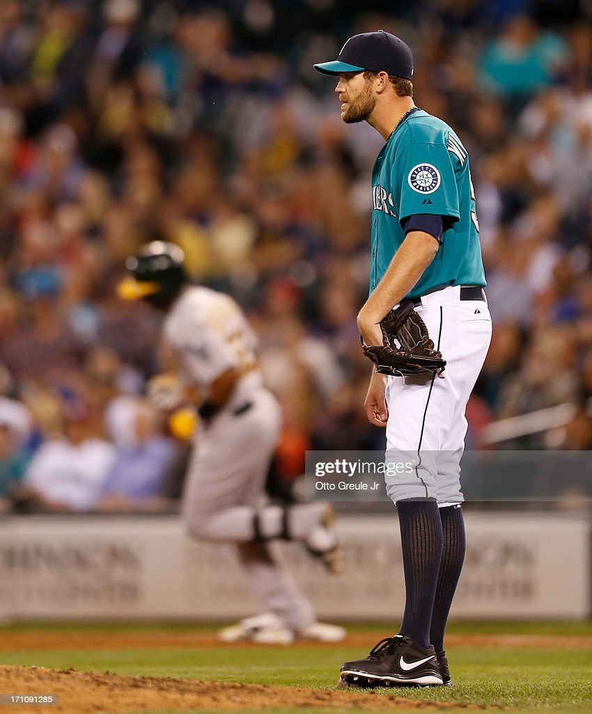 Closing pitcher Tom Wilhelmsen #54 of the Seattle Mariners reacts after giving up a two-run homer to Yoenis Cespedes #52 of the Oakland Athletics in the ninth inning at Safeco Field on June 21, 2013 in Seattle, Washington. The Athletics defeated the Mariners 6-3.