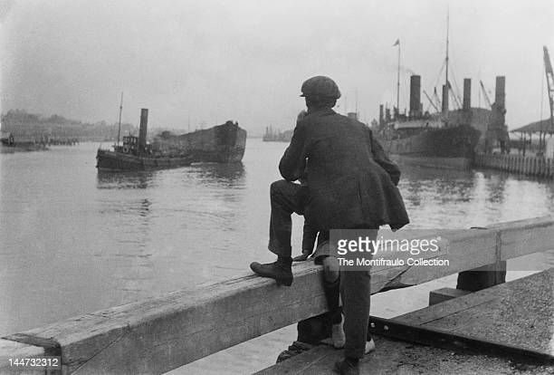 Cloth capped workman with young boy in shorts watching a tug boat pulling a barge along the River Thames with a steam ship and harbour cranes seen in...