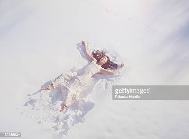 Clothed woman laying in the snow