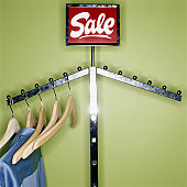 Clothes and wooden hangers hanging on sale rack, close-up