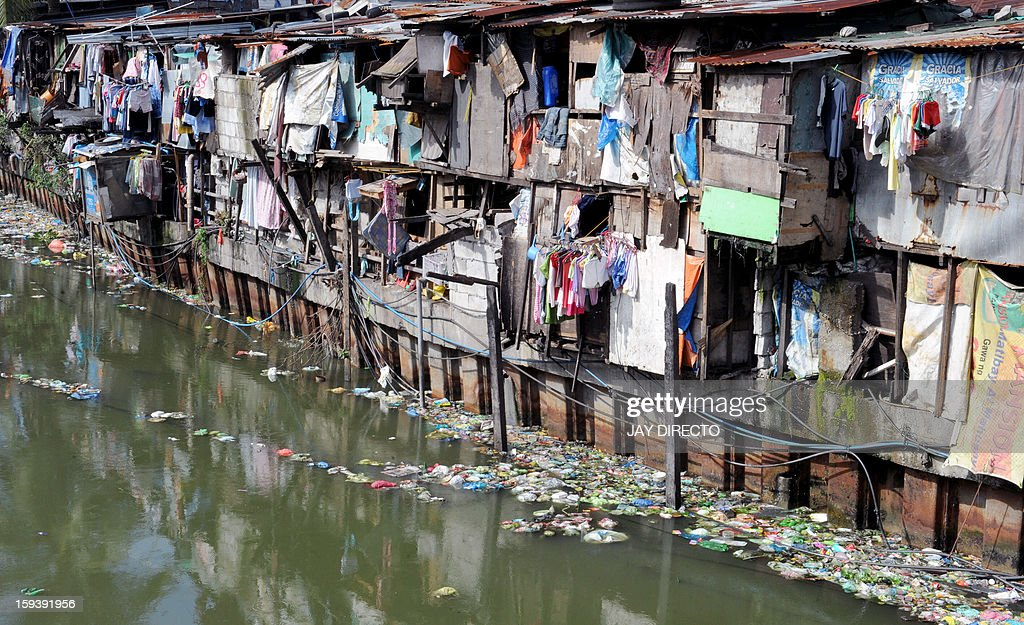 Clothes are hung to dry on lines outside shanty homes on the banks of a waterway in Manila on January 13, 2013. The Philippine government plans to move about 100,000 squatters from their homes on crucial waterways in Manila by June for their own safety and as a flood control measure, an official said on January 12. AFP PHOTO / Jay DIRECTO