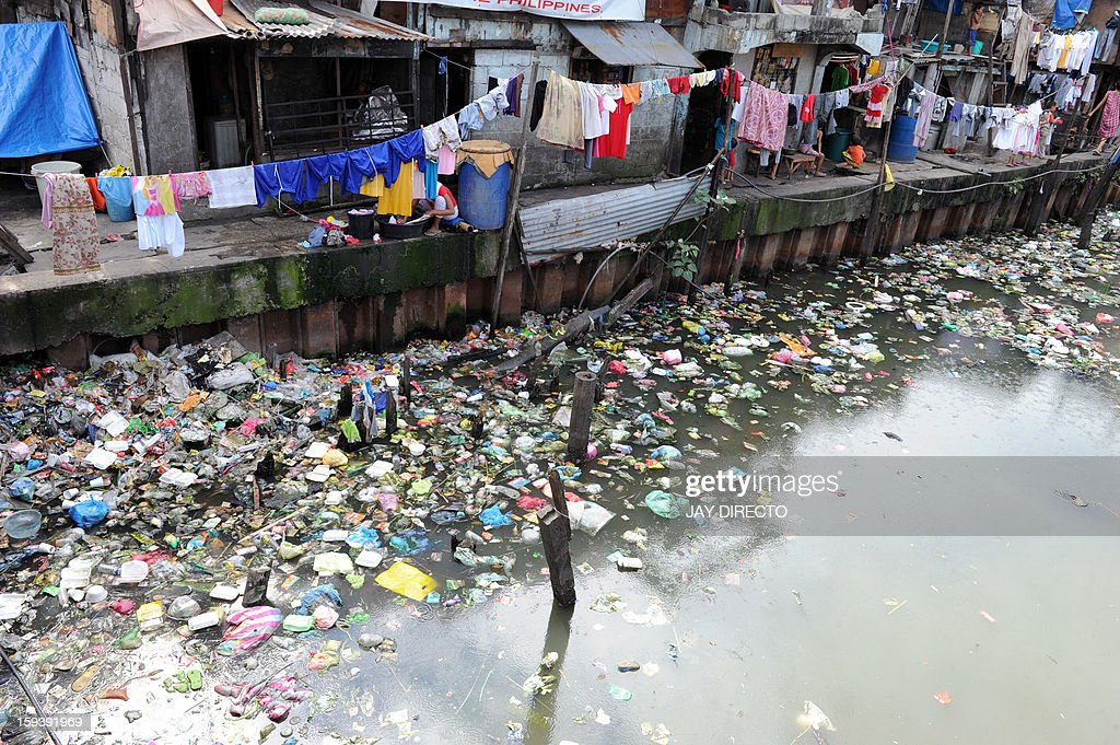 Clothes are hung to dry on lines outside shanty homes on the littered banks of a waterway in Manila on January 13, 2013. The Philippine government plans to move about 100,000 squatters from their homes on crucial waterways in Manila by June for their own safety and as a flood control measure, an official said on January 12. AFP PHOTO / Jay DIRECTO