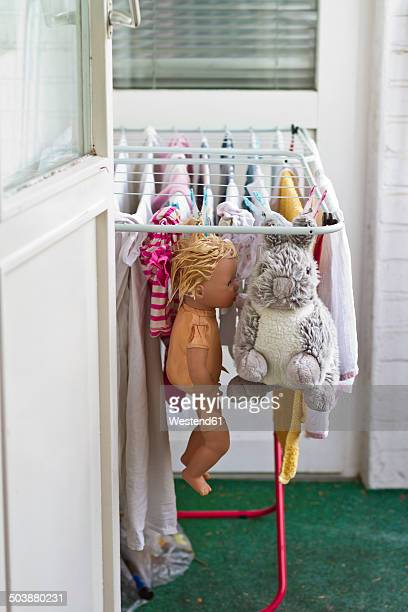 Clothes, doll and stuffed animal drying on clotheshorse at balcony