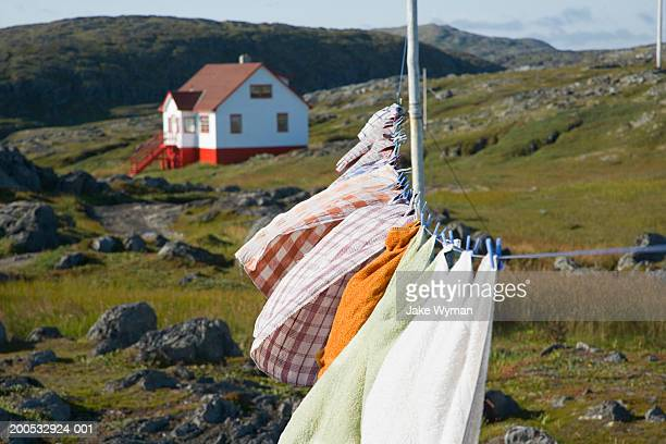 Clothes drying on clothesline, house in background