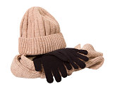 Clothes for a cold season: woolen cap, scarf and gloves. Cap and scarf of beige color, glove black. The object is isolated on a white background
