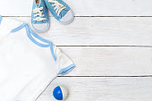 clothes for the kid and shoes on a white wooden background