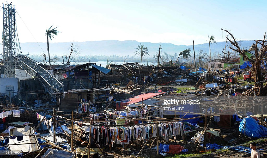 Clothes hang next to destroyed houses and toppled trees in Cateel town, Davao Oriental province on December 11, 2012 in the aftermath of Typhoon Bopha. The United Nations launched a 65 million USD global appeal on December 10 to help desperate survivors of a typhoon that killed more than 600 people and affected millions in the southern Philippines. AFP PHOTO / TED ALJIBE